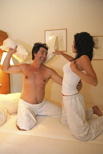 couple in love at bedroom making pillow fight