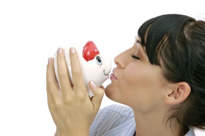 junge Frau kuesst ihr Sparschwein, young woman kissing piggybank