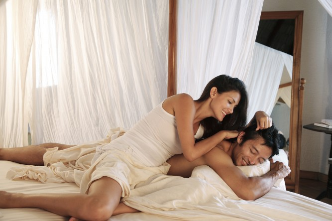 Couple in bed at Coco Palm Dhuni Kolhu Resort in Maldives