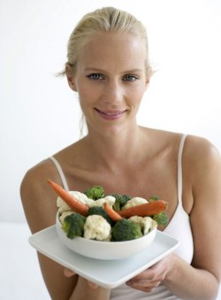portrait of woman holding a bowl of mixed vegetables