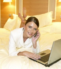 Junge Frau in Kostuem arbeitet mit dem Laptop im Hotelzimmer, young woman in suit working on notebook in hotel room