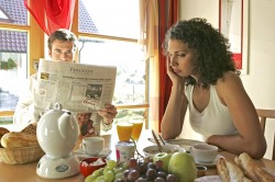 Paar beim together, togethernessen Fruehstueck er liest Zeitung sie ist sauer, couple having breakfast together he reads newspaper she is annoyed