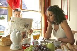 Paar beim together, togethernessen Fruehstueck er liest Zeitung sie ist sauer, couple having breakfast together he reads newspaper she is annoyed