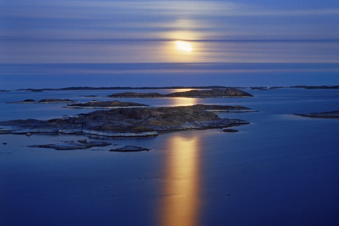 sweden, full moon over stora nassa island group in stockholm archipelago