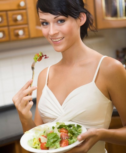 Young woman in kitchen eating her meal