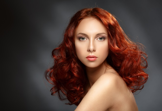 Portrait of a young ginger woman on a dark background. Low key. Long Curly Red Hair.