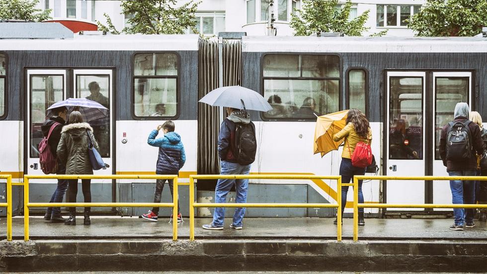 Oameni cu umbrele in statie la tramvai