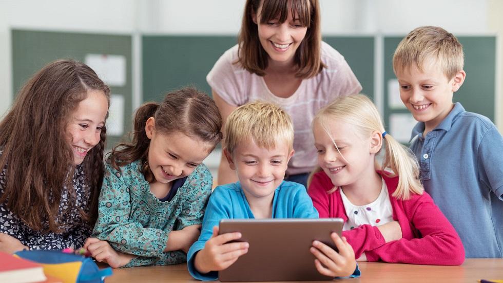 copii la scoala invatand de pe manualele digitale